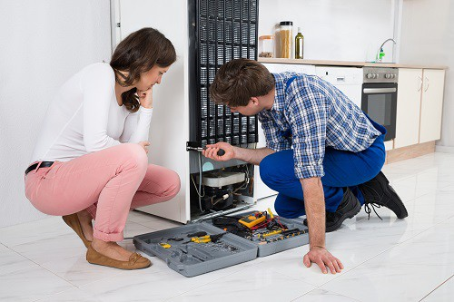 Young Repairman Repairing Refrigerator In Front Of Beautiful Woman